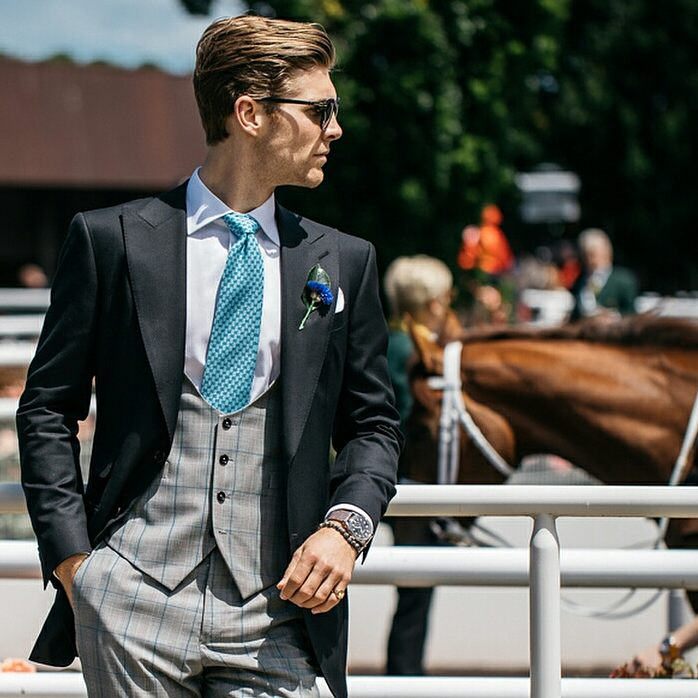 Gentleman in a three piece suit at the horse races wearing sunglasses and a signet ring