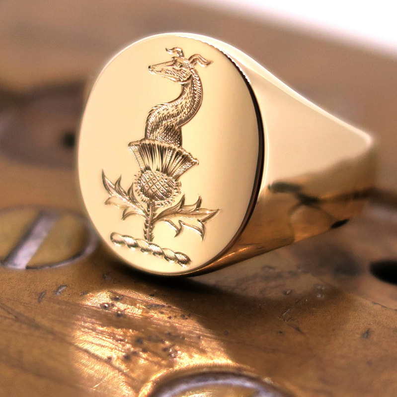 Surface engraved Crest on a yellow gold Oxford Oval signet ring.  Greyhound and thistle Crest.