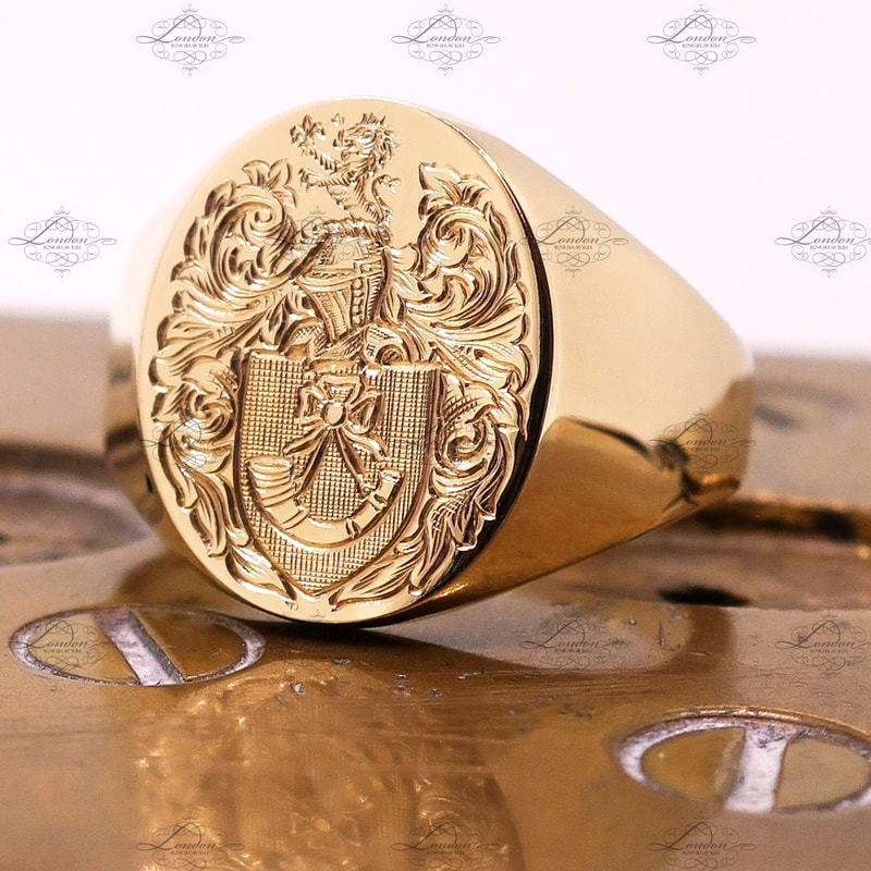 Yellow gold signet ring hand engraved with a surface Coat of Arms, sitting on engraver clamps