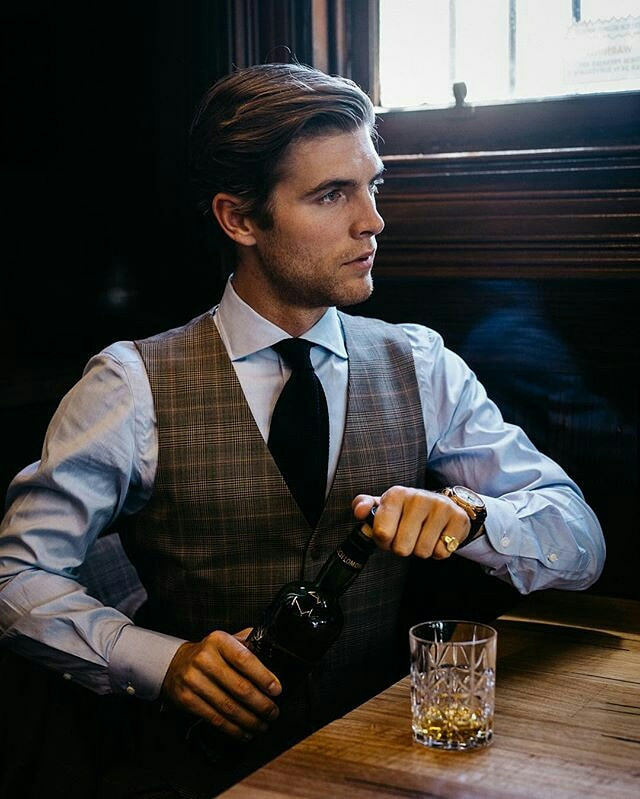 Gentleman wearing a shirt and waistcoat, pouring a whisky wearing a signet ring