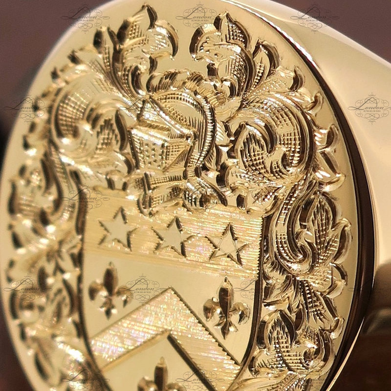 Detailed close up photo of a surface engraved coat of arms on a yellow gold oxford oval signet ring