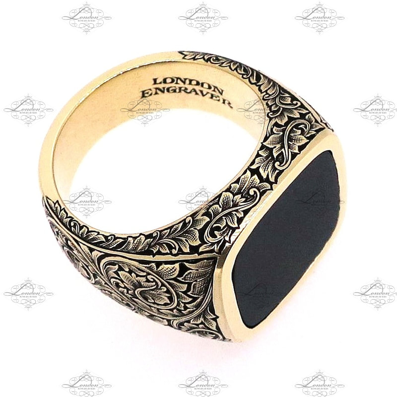 Yellow gold signet ring set with onyx, cushion shape, with hand engraved floral and scroll patternwork on shoulders and shank