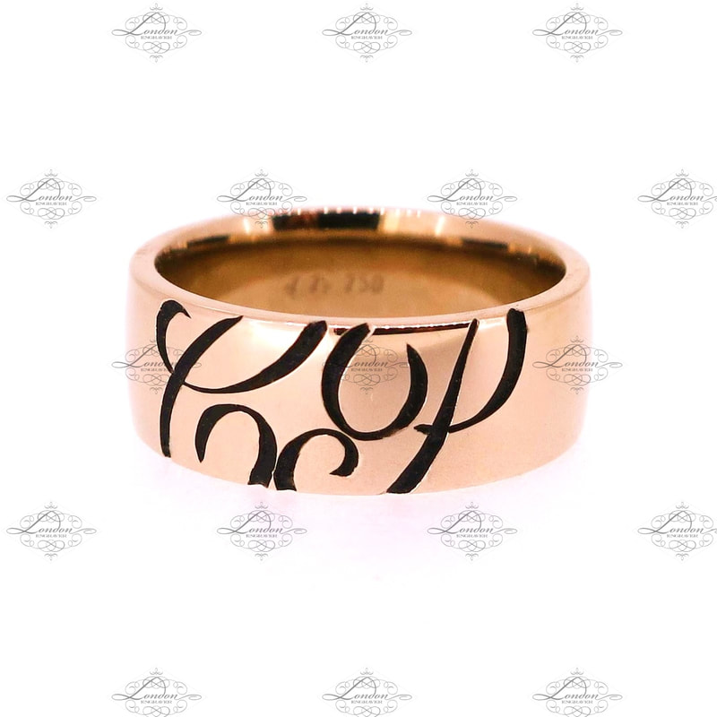 Initials CP engraved on the outside of a rose gold wedding band, with black enamel