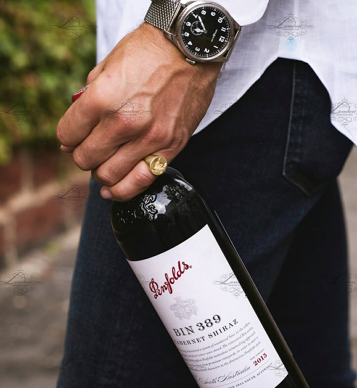 Man holding a bottle of Penfolds red wine, wearing a signet ring, Bin 389 Barossa Valley South Australia