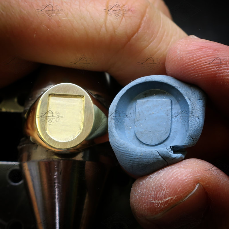 checking the progress of a seal engraving, using plasticine to check the cuts which have been engraved on a yellow gold signet ring