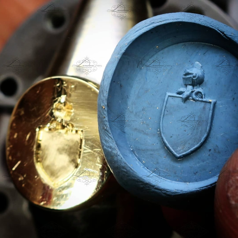 using plasticine to check the progress on a seal engraved coat of arms on a yellow gold signet ring