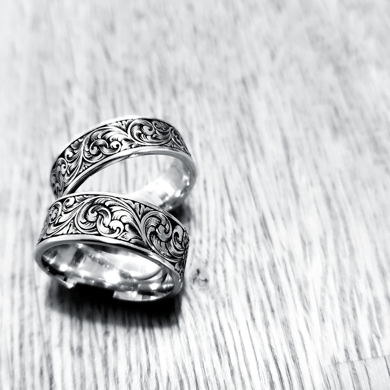 A pair of matching wedding rings with hand engraved scrollwork