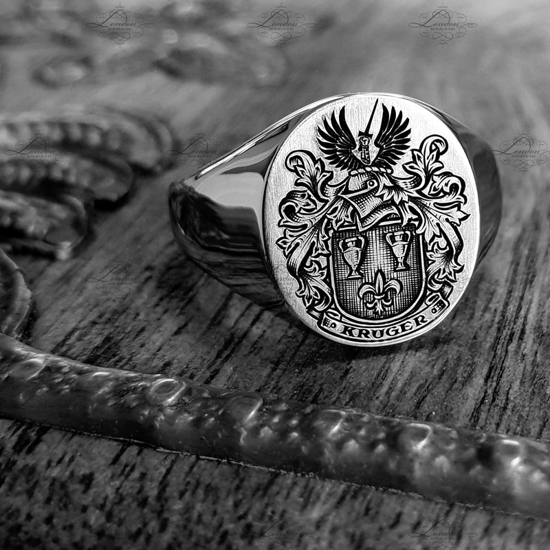 Surface engraved Kruger Coat of Arms, with black enamel. 12x14 Oxford Oval signet ring.