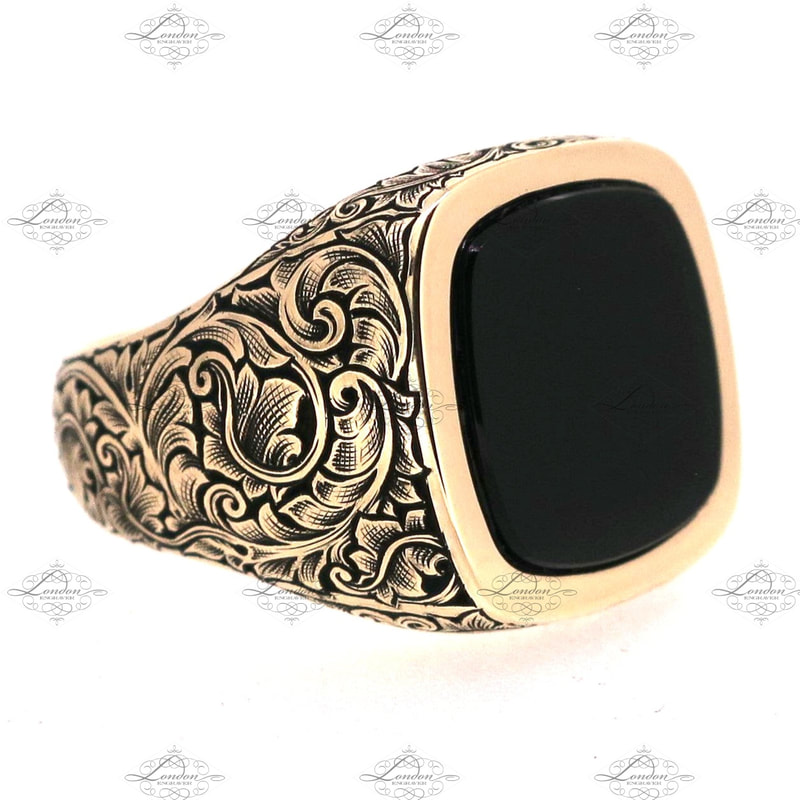 Yellow gold stone set cushion shaped signet ring set with onyx.  Hand engraved bespoke shoulder scroll patternwork